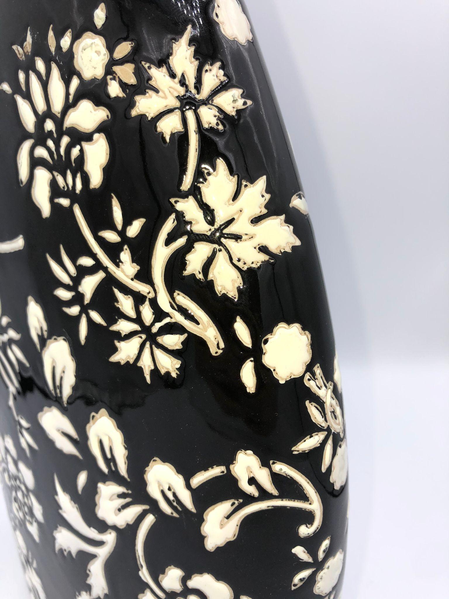 Jarrón de porcelana color negro con flores blancas
